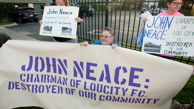 Dora Cornette, top left, Beverly Cairnes, center and Elsie Day, right, of the  Pleasant Ridge neighborhood of Charlestown, protest on the west side of Slugger field where the LouCity FC soccer team was playing. The group blames the team's chairman, John Neace, for helping Charlestown to destroy their homes.