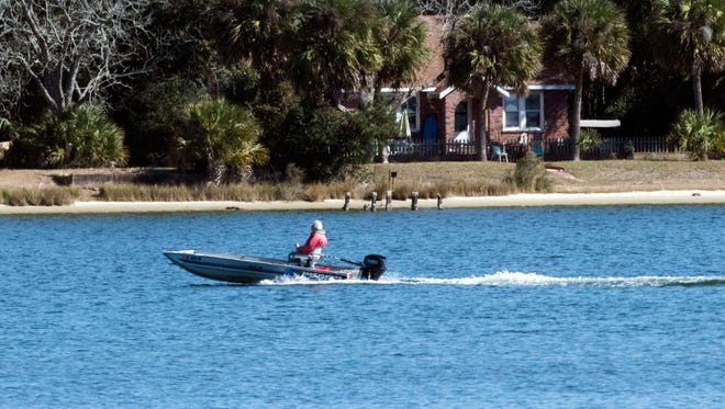 A boater glides through the water at Bayou Grande on Tuesday, Jan. 23, 2018. Escambia County is pushing for five new boating regulatory zones that would require boaters to slow down inside the designated areas. The proposed zones include a portion of Bayou Grande surrounding Pensacola Naval Air Station.