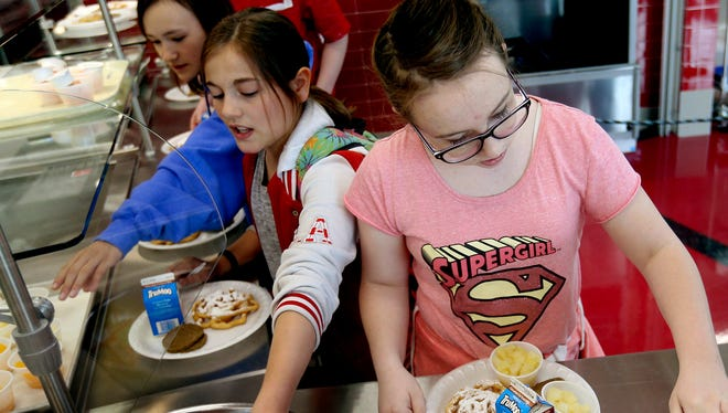 In a Friday, May 19, 2017 photo, Cara Hjorth, 6th-grader, right, inputs her student number to pay for lunch at Mount Jordan Middle School in Sandy, Utah. Canyons School District administrators are proposing that the school board adopt a policy that takes a kinder, gentler approach to school nutrition service to children whose accounts are in arrears.