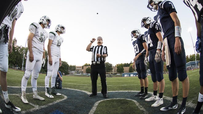 The referee tosses the coin in the air during the high school football game between the Rice Green Knights and the Burlington Seahorses at Burlington high school on Friday night September 9, 2016 in Burlington. (BRIAN JENKINS/for the FREE PRESS)