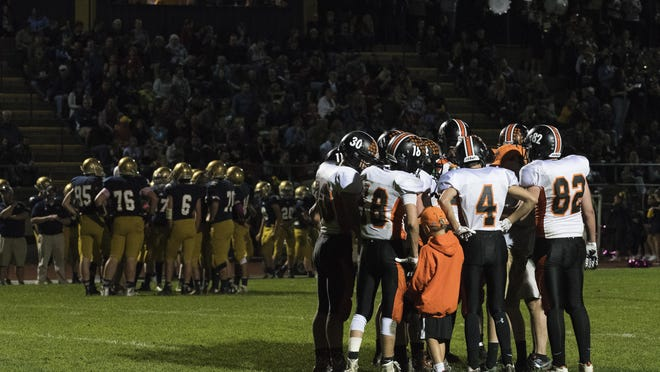 The teams huddle together during a time out during the high school football game between the Middlebury Tigers and the Essex Hornets at Essex High School on Friday night Octoer 7, 2016 in Essex.