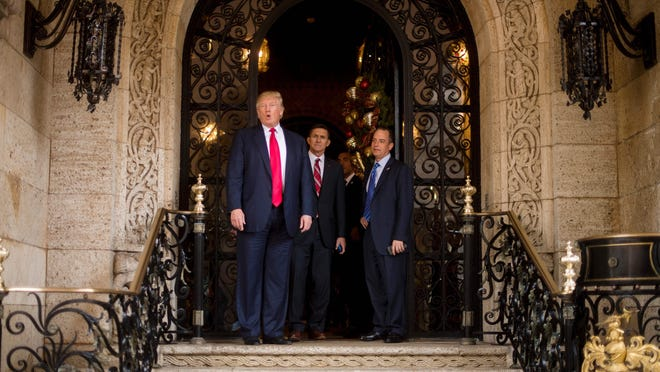 TOPSHOT - US President-elect Donald Trump (L) gestures as he speaks with Trump National Security Adviser Lt. General Michael Flynn (C) and Trump Chief of Staff Reince Priebus (R) at Mar-a-Lago in Palm Beach, Florida, where he is holding meetings on December 21, 2016. / AFP / JIM WATSON (Photo credit should read JIM WATSON/AFP/Getty Images)