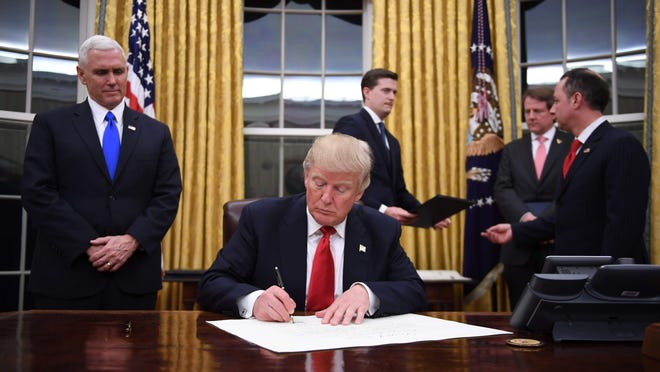 President Donald Trump signs a confirmation for John Kelly as U.S. Secretary of Homeland Security shortly after the inauguration Friday as Vice President Mike Pence (left) and White House Chief of Staff Reince Priebus look on in the Oval Office.