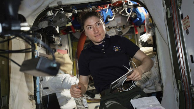 In this April 8, 2019 photo made available by NASA, astronaut and Expedition 59 Flight Engineer Christina Koch works on U.S. spacesuits inside the Quest airlock of the International Space Station.