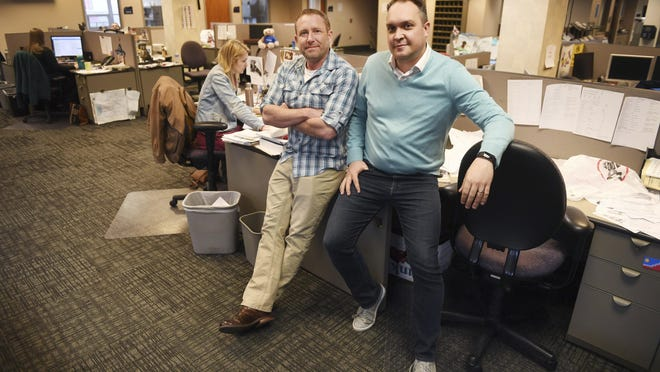 In this April 9, 2019, photo, Argus Leader investigative reporter Jonathan Ellis and news director Cory Myers in the newsroom in Sioux Falls, S.D.
