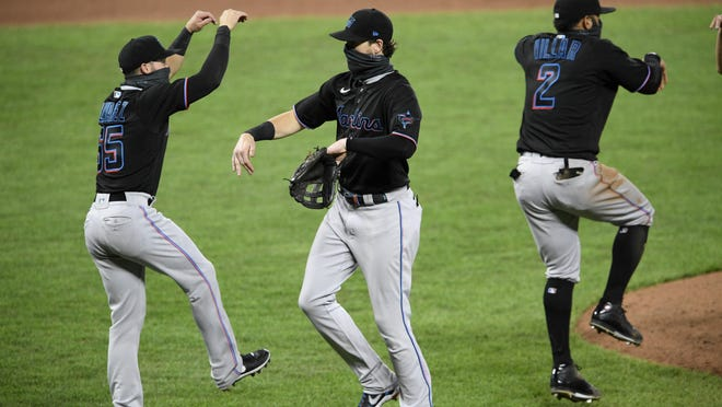 Miami Marlins' Brian Anderson, center, Eddy Alvarez, left, and Jonathan Villar (2) celebrate after a win against the Baltimore Orioles on Thursday.