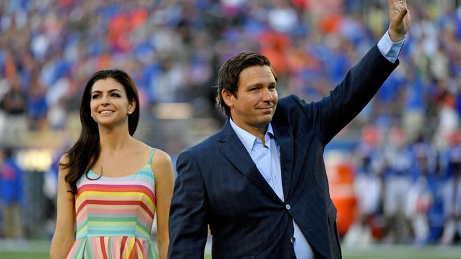 Florida Gov. Ron DeSantis and his wife, Casey, on the field when the Miami Hurricanes and Florida Gators met at Camping World Stadium in Orlando last August.