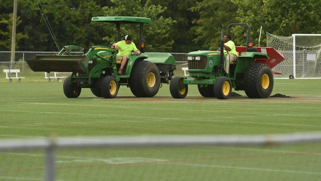 Crews work on the field at Legion Stadium in Wilmington, N.C., Thursday June 11, 2020. Despite entering its window for replacement, the artificial turf won't be updated until at least 2023.