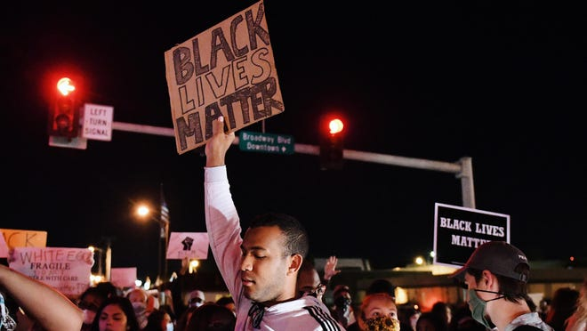 "A man holds up a ""Black Lives Matter"" sign during a protest Monday night in Columbia."