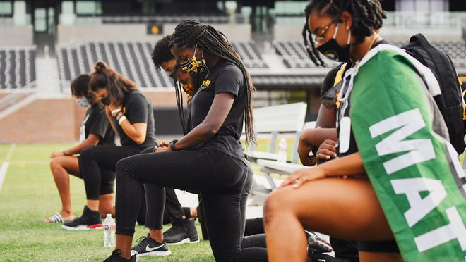 Members of the Mizzou Black Student Athlete Association take a knee at Faurot Field during the March With Mizzou protest on Wednesday evening.
