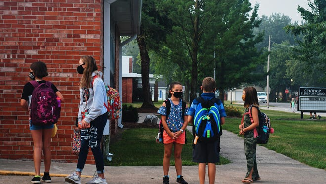 Children wearing masks huddle around before school starts at Chance Elementary School in Centralia on Friday morning. Cases among people under 24 make up 75 percent of cases in Boone County in the past week, but few are in the Centralia area.