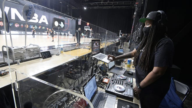 Nicole Mosley, who goes by her stage name DJ Heat, performs music behind glass partitions during warmups before a WNBA basketball game between the Chicago Sky and the New York Liberty, Tuesday, Aug. 25, 2020, in Bradenton, Fla. Performing in the WNBA bubble at games presents a new experience for DJs and announcers since there are only a handful of people in attendance at games besides the players.