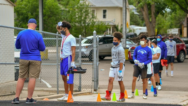 Players lineup to have their temperature taken outside the football field at Central High School on June 25.