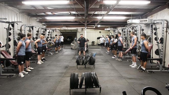 Roosevelt strength coach Dane Burk leads practice in the weight room to start preseason workouts on Monday at Roosevelt. The Eagles had scheduled a Midnight Madness practice, but had to move inside due to inclement weather.
