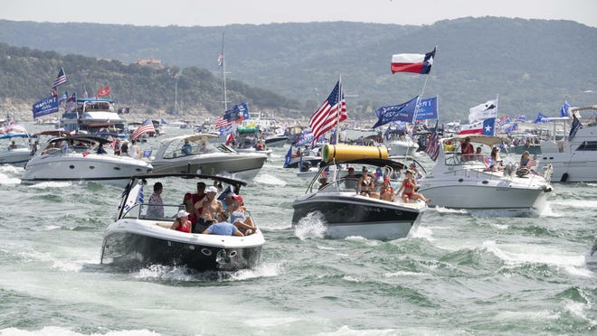 Boats flying flags honoring President Donald Trump crowd Lake Travis during a boat parade Saturday that attracted hundreds of watercrafts.