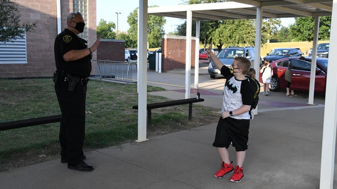 Denison Police Officer Kevin Venton took time out to help welcome students and staff back to Terrell Elementary school in 2020. Visiting with Venton are Terrell staff member Jessica Horne and student Case Bussey.