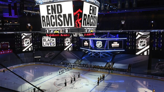 """An """"End Racism"""" message is displayed before Game 3 of an NHL hockey second-round playoff series between the Tampa Bay Lightning and the Boston Bruins, Wednesday, Aug. 26, 2020, in Toronto. Game 4 of the series, postponed from Thursday in solidarity with ongoing protests over the police shooting of Jacob Blake in Wisconsin, will be played Saturday, Aug. 29, 2020."""