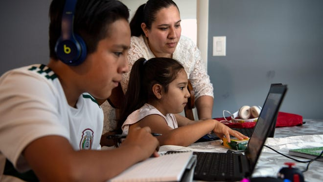 (Left) Carlos Cano, an eighth grade student, and his sister Caia Cano, a kindergarten student, during an online class as their mother Adriana Medina looks on at their home in Neptune on Thursday, September 17, 2020.