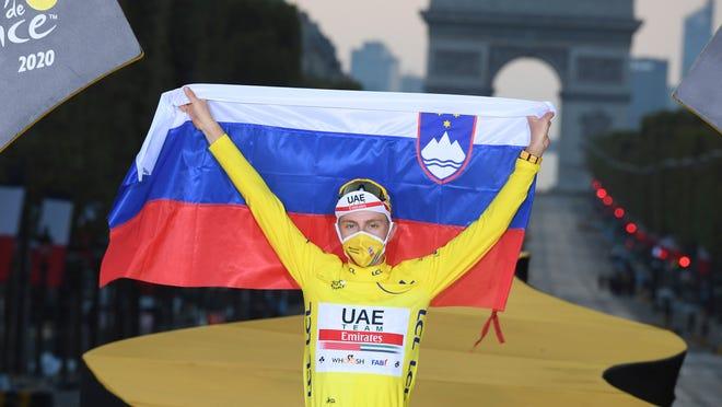 Tour de France winner Tadej Pogacar celebrates his victory on the podium with a Slovenian flag.