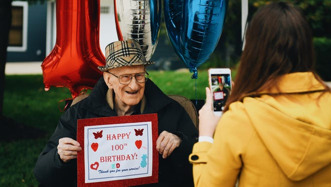 Ed McComb poses for a photo with a sign made for him by a neighbor on his 100th birthday. McComb was honored with a celebratory drive-by from friends, family, and members of the community on Saturday afternoon in Columbia.