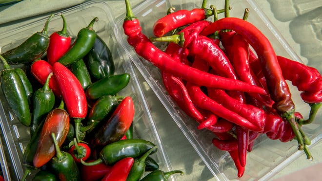 Bright red cayenne peppers, right, and jalapeno peppers draw attention to the Hartz Produce booth Saturday, Sept. 26, 2020 on the last day of the season for the weekly Peoria Riverfront Market.