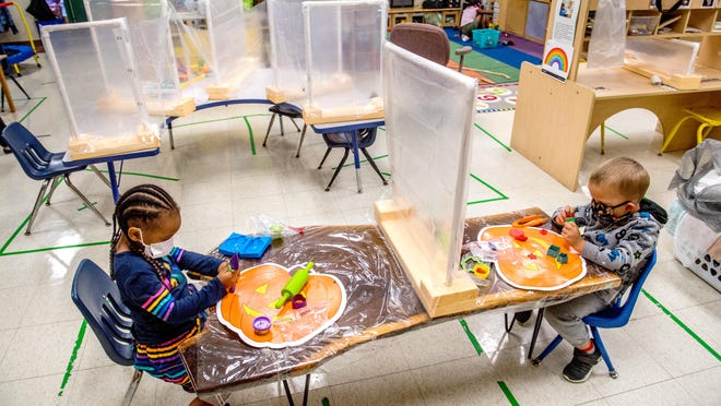 Nylaine Smith, left, and Cole Hardin, both 4, are separated by a homemade barrier and lots of plastic sheeting as they work in teacher Mary Keltner's classroom Thursday, Aug. 6, 2020 at Valeska-Hinton Early Childhood Education Center, 800 W. Romeo B. Garrett Avenue in Peoria. The school was the first in the Peoria area to resume classes with heavy COVID-19 restrictions.