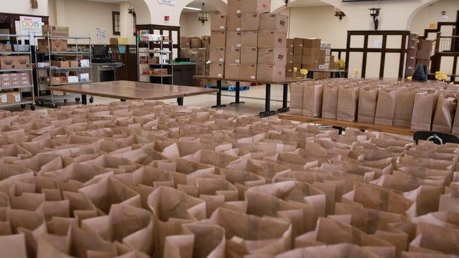 Bags are lined up ready to receive meals at Topeka High School for the USD 501 summer school meal program.
