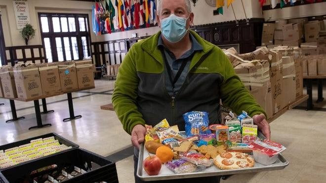 Chris Wagner, child nutritional services specialist for Topeka USD 501, shows a tray of food that will be offered to students as part of the summer meals program Friday at Topeka High School.