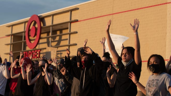 A group of protesters stand in a line with hands raised Tuesday night in front of Target and Cici's Pizza at West Ridge Plaza.