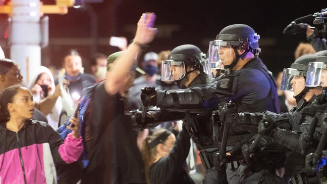 Kansas Highway Patrol officers force back protesters in front of the Law Enforcement Center at 4th Street and S. Kansas Avenue on Monday night.