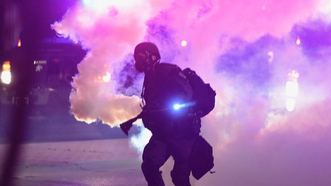 A Kansas Highway Patrol officer throws a canister of tear gas in downtown Topeka on Monday night. KHP was called to the scene after a group of protesters arrived at the Law Enforcement Center shortly after 10 p.m. and turned violent.