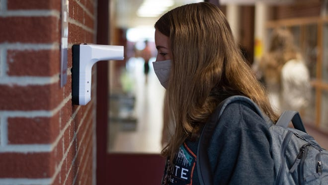 Students at Silve Lake High School get their tempature checked on a unit attached to the entryway Wednesday morning.
