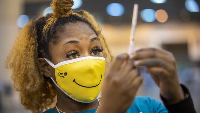 Medical assistant Keona Shepard holds up a dose of a COVID-19 vaccine before administering it Thursday at a mass vaccination site in New Orleans.