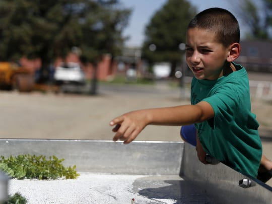 Aiden Winters, 7, points to where he thinks his house would be in relation to the river on a watershed demonstration trailer during the Aztec Through Time children's camp at the Aztec Museum and Pioneer Village.