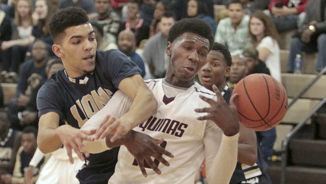 Aquinas' Melvin Grayson looses the ball as Leadership's Gary Whiteside comes over his back during the first half of their game Monday, Dec. 29, 2014 at Aquinas Institute.