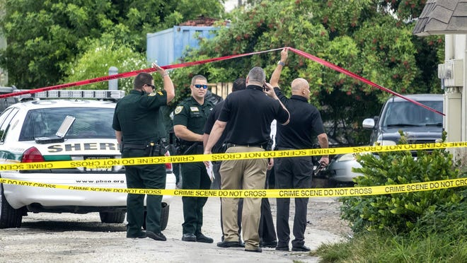 PBSO investigators enter the crime scene where a man was killed in Lake Worth Beach Wednesday morning, December 18, 2019.