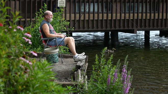 Stan Sawyer of Canton finds a comfortable spot to fish near the marina at Sippo Lake Park.