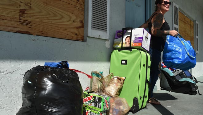 "Melissa Earles gathers her belongings while waiting for a ride to evacuate her home in the Pearly Sands apartments along Hernando Street on South Hutchinson Island on Friday, Sept. 8, as Hurricane Irma approaches Florida. ""It's stressful, the unknown, not knowing,"" Earles said about dealing with Hurricane Irma as she plans to ride out the storm inland in Fort Pierce."