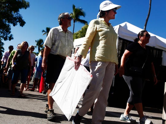 Art goers stroll 5th Ave. South during the 19th annual downtown Naples New Year's Art Fair on January 4, 2015, in Fla. Art vendors, local and international, filled the streets with their work for attendees of the event to look at or buy. (Dania Maxwell/Staff)