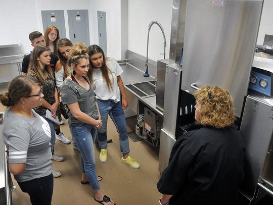 Advanced Culinary students listen as their instructor,