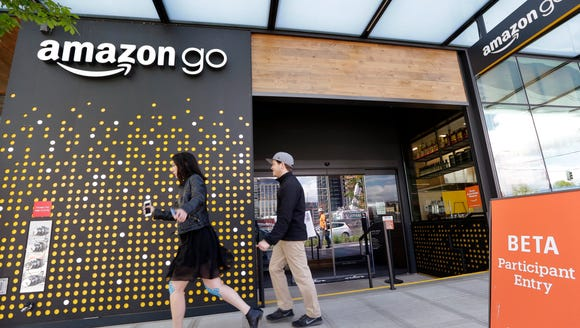 People walk past an Amazon Go store, currently open