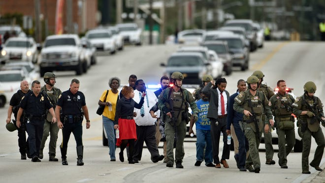 Police officers escort hostages safely across Edgewood Avenue West after a gunman held them during an attempted robbery at Community First Credit Union Thursday, Dec. 1, 2016, in Jacksonville, Fla. (Will Dickey/The Florida Times-Union via AP)