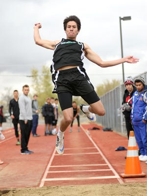 Farmington's Clayton Corley competes in the long jump at the Bill Slade Invitational on April 16 at Kirtland Central High School.