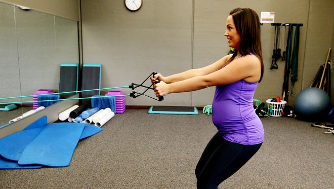 Christie Steiger demonstrates exercises a pregnant woman can do in this file photo from 2014. Brian Schroeder, Fitness Director at Prairie Life Fitness, helped her develop a fitness plan.