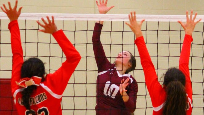 Tularosa's Gracie Hooten, center, hits a ball in between Loving's Alyssa Carrasco (22) and Briana Rodriguez (21) on Thursday night at the Michael Dorame Gymnasium during the District 4-3A semifinal.