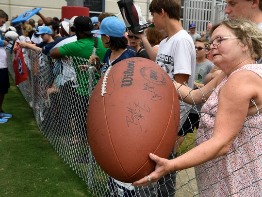 Titans fan Julie Ferrell waits to get an autograph from general manager Jon Robinson after training camp practice at Saint Thomas Sports Park Tuesday, Aug. 1, 2017 in Nashville, Tenn.