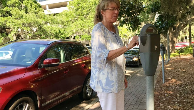 Marianne Trussell, a local attorney, feeds a parking meter Friday on Park Avenue.