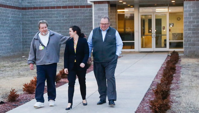 Brad Jennings, left, walks out of the Texas County Jail in Houston, Missouri, with Elizabeth Ramsey and J. Dwight McNiel after being released on bond from the South Central Correctional Center.