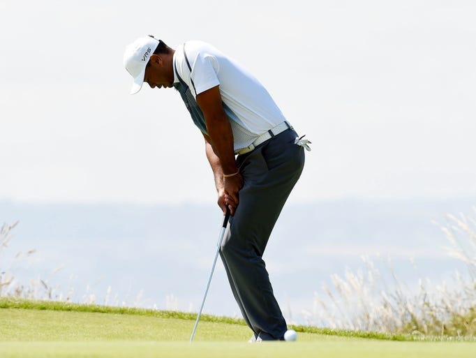 Tiger Woods leans on his putter after missing a putt on the 14th during his first round at The 143rd Open Championship at the Royal Liverpool Golf Club.