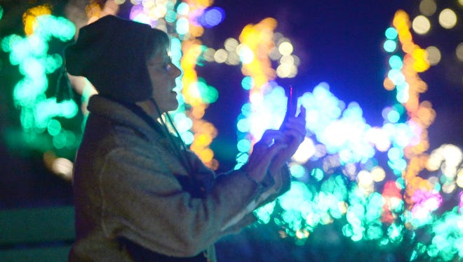 Carol LaBorde of Loveland takes a photo at the annual Garden of Lights show at the Gardens at Spring Creek in 2013.